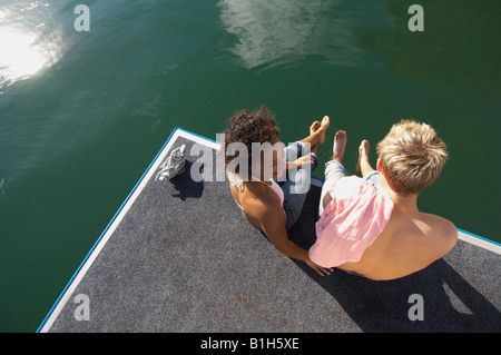 High angle view of a young couple sitting on a pier - Stock Photo