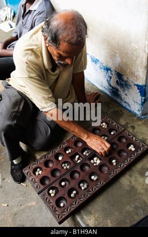 Man sitting playing a game Stonetown Zanzibar, Tanzania, East Africa. Amyn Nasser amynnasser [room for copy] artisan - Stock Photo