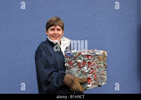 Council employee holding recycled trash, refuse, crushed, metal, garbage,  beverage Aluminium cans crushed into - Stock Photo