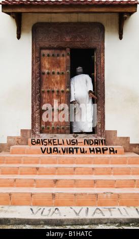 Man entering doorway in Stonetown Zanzibar, Tanzania, East AFRICA - Stock Photo