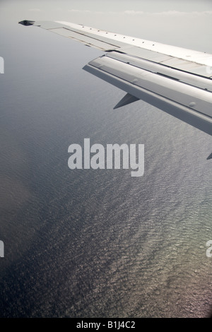 High level oblique aerial view of aircraft wing flying over sea - Stock Photo