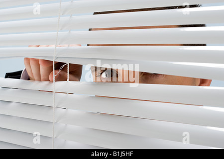 Man looking through blinds - Stock Photo