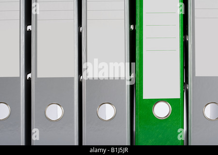 Green folder and grey folders - Stock Photo