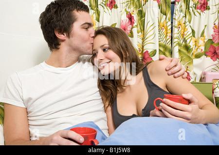 A teenage boy kissing a teenage girl on the head - Stock Photo