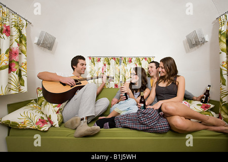 A teenage boy playing the guitar for his friends - Stock Photo