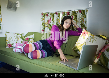 A teenage girl listenign to music on a laptop - Stock Photo