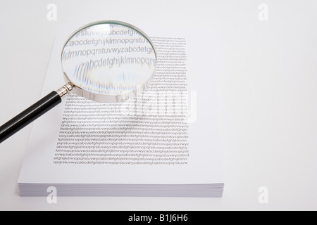Magnifying glass and a stack of paper - Stock Photo