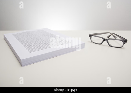 Eyeglasses and a stack of paper - Stock Photo