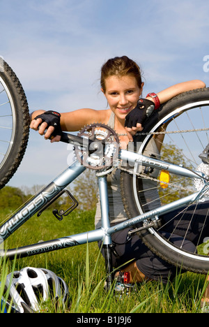 young woman with helmet, reparing her mountainbike in a meadow - Stock Photo