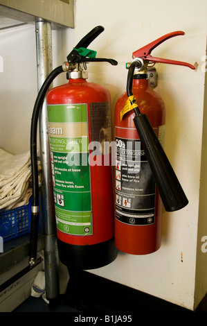 Safety equipment: two red fire extinguishers one foam one carbon dioxide in hotel cafe restaurant kitchen UK - Stock Photo