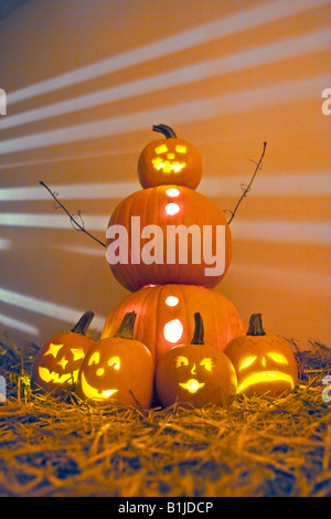 Jack-O-Lantern man with smaller Jack-O-Lanterns on the ground in front of him in hay on the ground. - Stock Photo