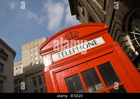 angeled detail of red phone box with blue sky - Stock Photo