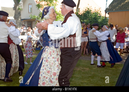Elderly couple perform folk dance in traditional dresses during celebration of Swedish National Day - Stock Photo