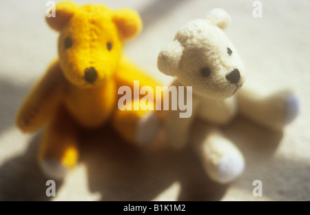 Impressionistic close up of one yellow and one white teddy bear sitting next to each other in sun with window bar - Stock Photo