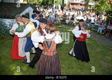Elderly couples perform folk dance in traditional dresses during celebration of Swedish National Day - Stock Photo
