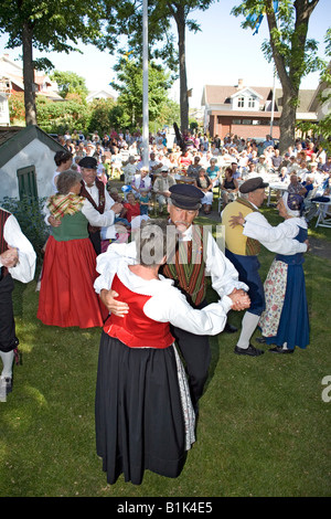 Elderly couples perform folk dance in traditional dresses - Stock Photo