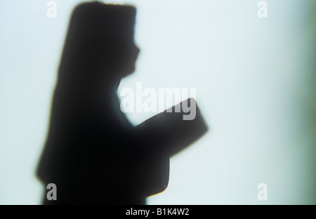 Impressionistic close up of model of nun in profile singing or reading from hymn book or Bible silhouetted against - Stock Photo