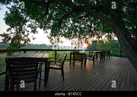The outdoor dining area with a view over the Sand River at dawn from at Singita Boulders Lodge, Sabi Sand Game Reserve - Stock Photo