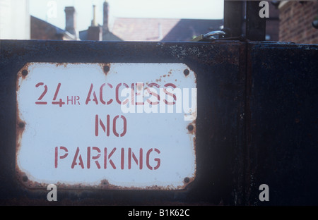 Red and white notice on rusting solid metal and padlocked gates stating 24 hr Access No Parking with rooftops visible - Stock Photo