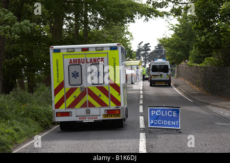 paramedic private ambulance passes police accident temporary sign in the middle of the road at the scene of a road - Stock Photo