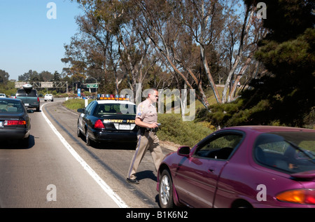 Highway Patrol Police stop vehicle on Freeway but Police have a flat tire tyre - Stock Photo