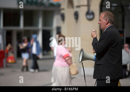 christian fundamentalist preacher with microphone and loudspeaker on sunny afternoon preaching in main shopping - Stock Photo