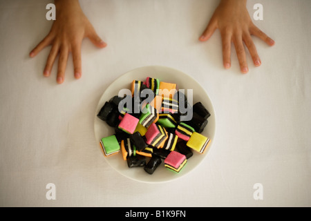 Hands of child six year old boy waiting for permission to take a candy - Stock Photo
