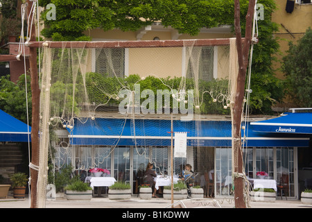 Volosko Istria Croatia Europe Old villas and restaurants around harbour with fishing net hanging out to dry in fishing - Stock Photo