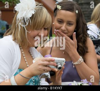 Wedding guests looking at digital photos on camera Wales UK - Stock Photo