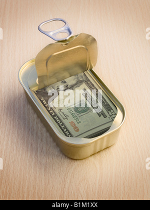 Ring Pull Tin containing  20 Dollar notes on wooden surface - Concept - Stock Photo