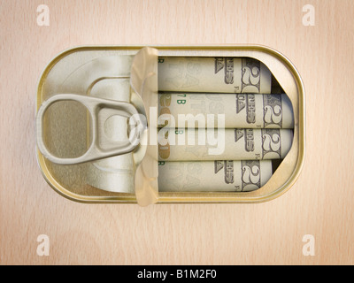 Plan view of a Ring Pull Tin containing rolled 20 Dollar notes on wooden surface - Concept - Stock Photo