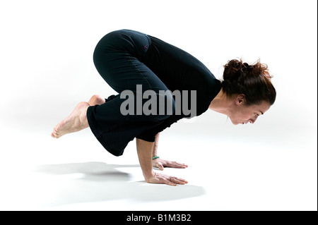 profile view of a woman practicing the crow pose - Stock Photo