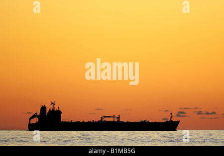 Silhouette of a large tanker ship at sunset - Stock Photo