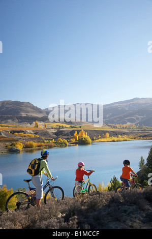 Mountain Bikers Lake Dunstan and Autumn Colours Bannockburn Central Otago South Island New Zealand - Stock Photo