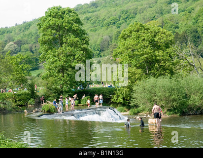 People enjoying a sunny day at the weir on the River Avon in Claverton Village, Bath UK - Stock Photo