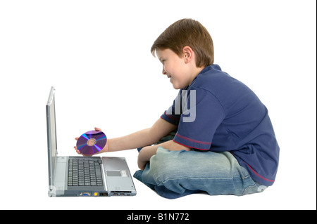 Happy young boy sat cross legged about to insert a DVD into a laptop isolated on a white background - Stock Photo