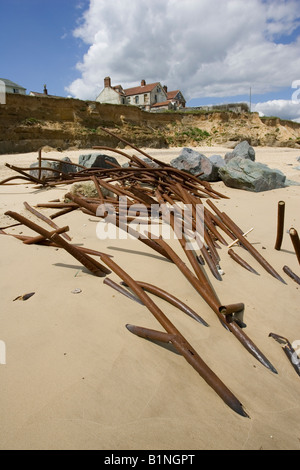 House on cliff edge and remains of sea defences after severe coastal erosion Happisburgh North Norfolk Coast UK - Stock Photo