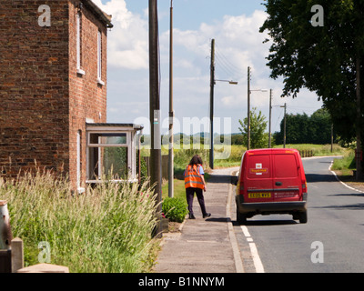 Post woman and red Post van on rural delivery round in East Yorkshire England UK - Stock Photo