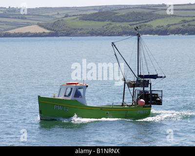 Small fishing boat heading out to sea - Stock Photo