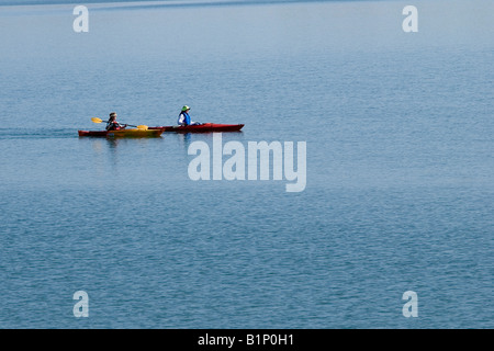Two female kayakers paddle across the serene Boulder Reservoir in Boulder Colorado - Stock Photo