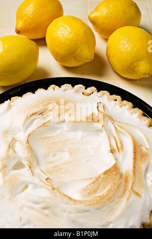 Lemon meringue pie with lemons - Stock Photo