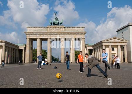 Children playing football in front of the Brandenburger, Tor Branderburg gate in Pariser Platz square Berlin Germany - Stock Photo