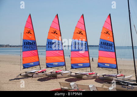 4 catamarans with brightly coloured sails on a beach  in Brittany. - Stock Photo