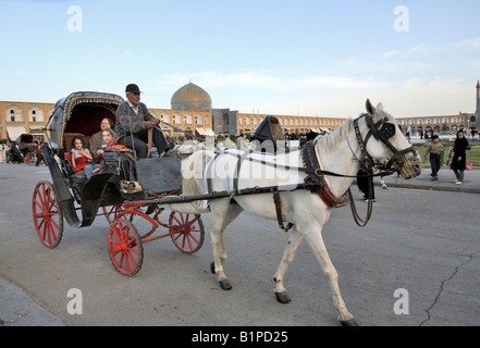 Popular horse and carriage rides taking vistors around Khomeini, Square Esfahan. - Stock Photo