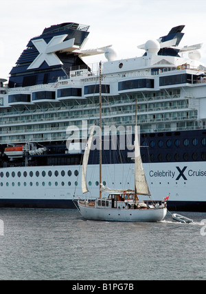 Sailing yacht passing a very large cruise ship on the River Clyde, Glasgow, Scotland. - Stock Photo
