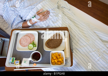 Sick senior with his supper in the hospital bed of a hospital ward for private insurance patients of the category - Stock Photo