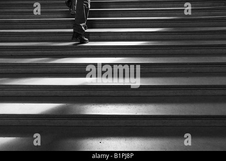 Walking up a wide set of stone stairs - monochrome - Stock Photo