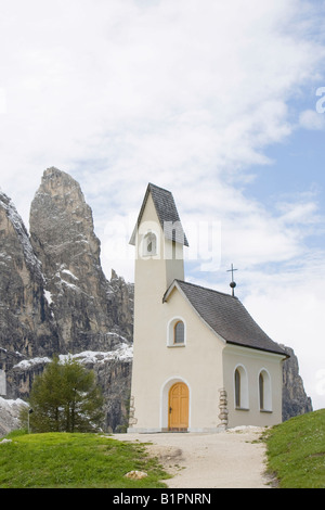 A mountain chapel above the Gardena Pass near Corvara in the Italian Dolomites with the sella mountains behind - Stock Photo