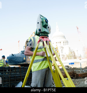 Surveyor working in construction site. No model release required, as full head crop makes man unrecognizable - Stock Photo