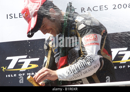 Australian Cameron Donald enjoying the champagne bath from his fellow competitors after the Senior TT garlanding - Stock Photo